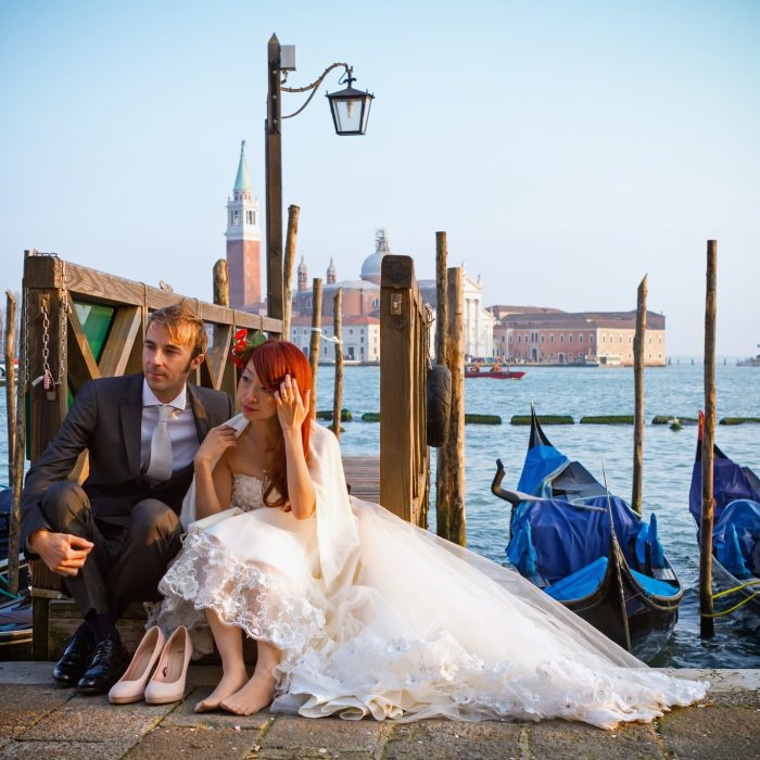 VENICE, ITALY - FEBRUARY 27, 2014: Unidentified person, wedding couple sitting on a pier in Venice, Italy on February 2014.